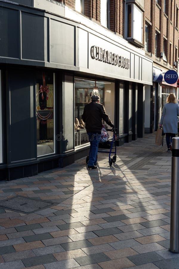 Uomo anziano sulla via principale Inghilterra in ombra fotografia stock libera da diritti