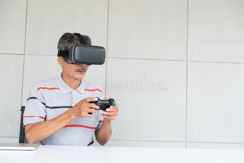 Uomo anziano in vetri di realt? del vr di realt? virtuale con il gioco del gioco immagini stock