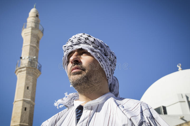 Uomo arabo che sta sotto il minareto di una moschea immagine stock libera da diritti