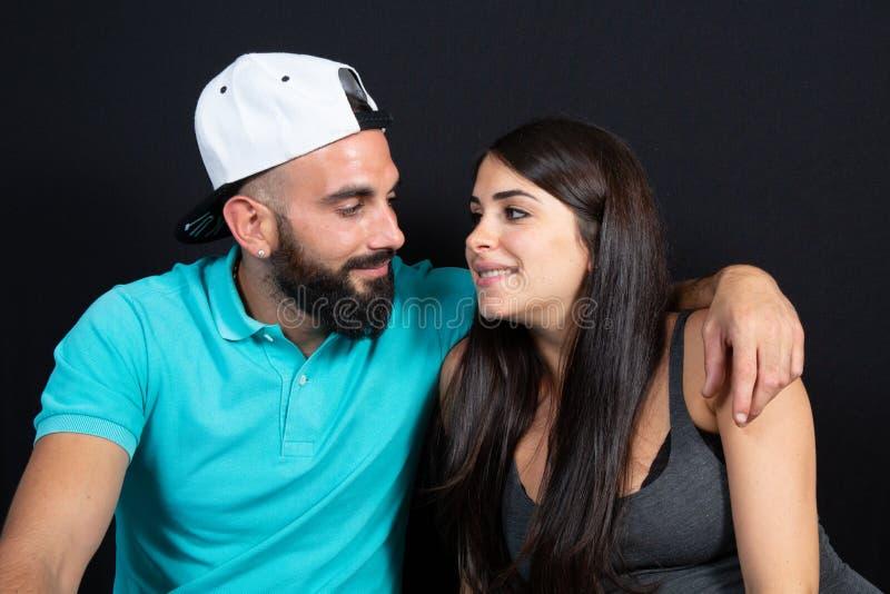Uomo arabo delle coppie con barbuto e cappuccio con l'Arabo grazioso di bellezza della donna nello stile di vita sopra fondo nero fotografia stock