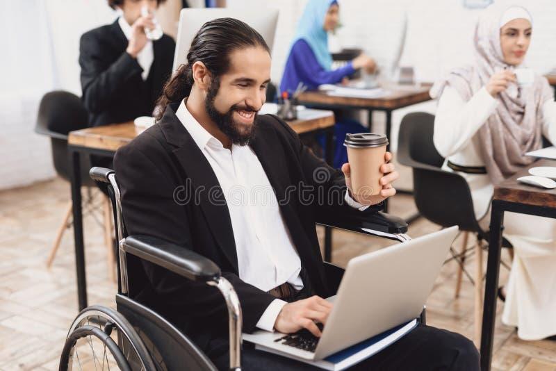 Uomo arabo disabile in sedia a rotelle che funziona nell'ufficio L'uomo sta lavorando al computer portatile ed al caffè bevente fotografie stock libere da diritti