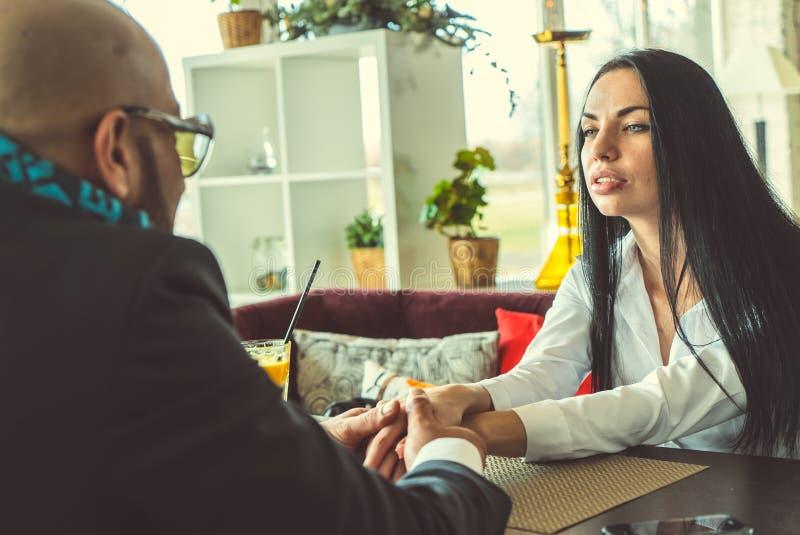 Uomo arabo e ragazza che si tengono per mano nel ristorante fotografie stock