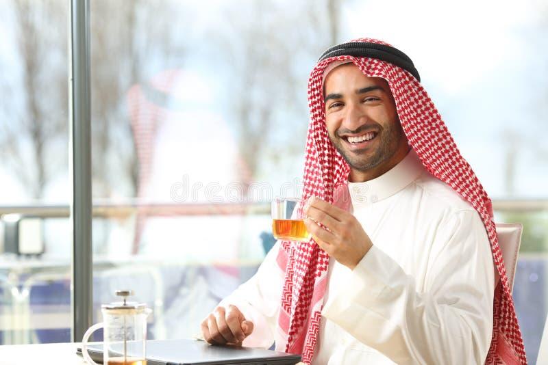 Uomo arabo felice con una tazza di tè che guarda la macchina fotografica fotografia stock