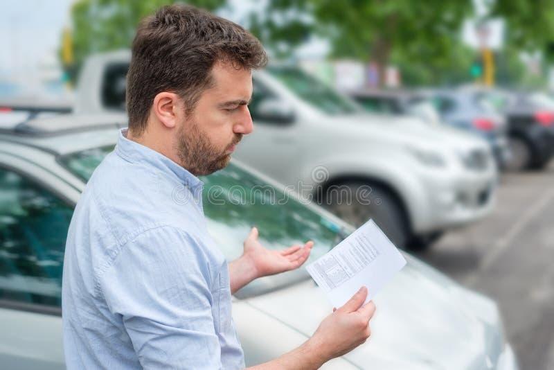 Uomo arrabbiato che considera il biglietto di parcheggio disposto sotto il tergicristallo fotografie stock libere da diritti