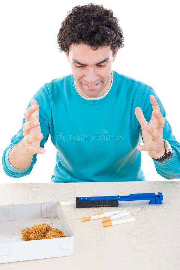 Uomo arrabbiato che fa le sigarette con il dispositivo per il sigaro e il tobacc asciutto immagine stock libera da diritti