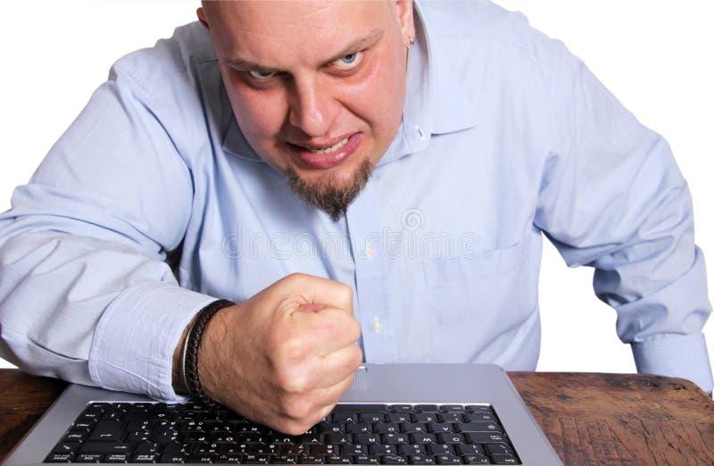 Uomo arrabbiato davanti al calcolatore immagine stock