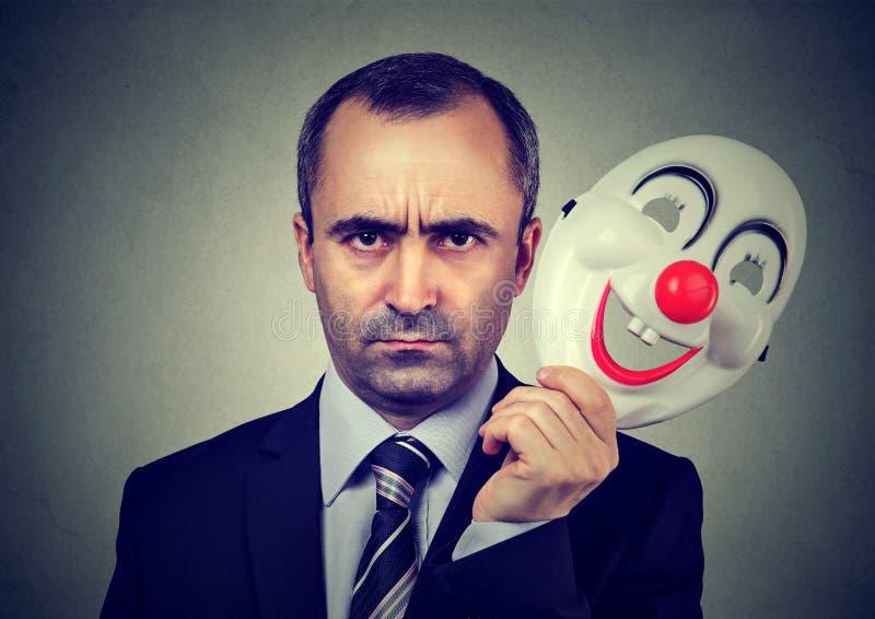 Uomo arrabbiato di affari che decolla la maschera felice del pagliaccio immagini stock libere da diritti