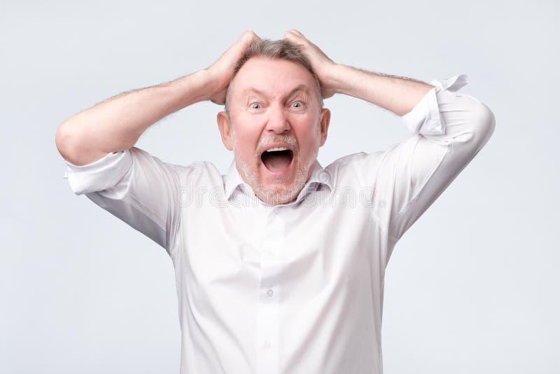Uomo arrabbiato senior con la mano alla testa sulla parete dello studio immagine stock