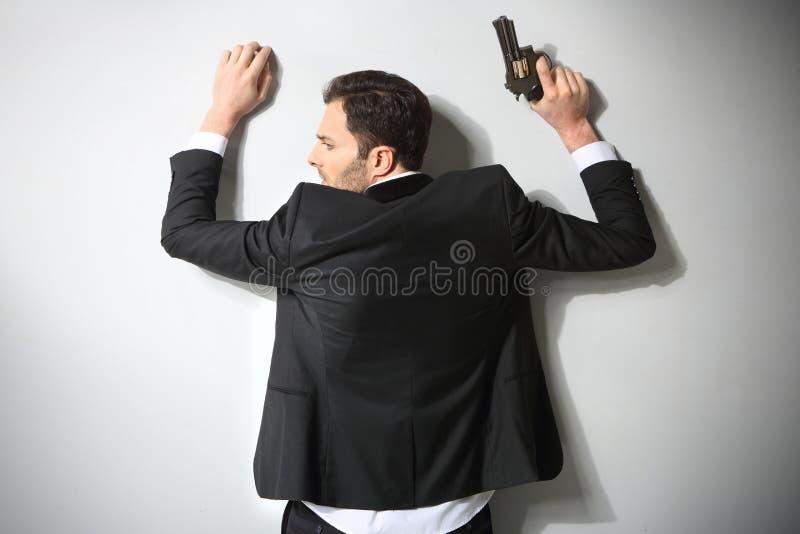 Uomo arrestato con la pistola immagine stock