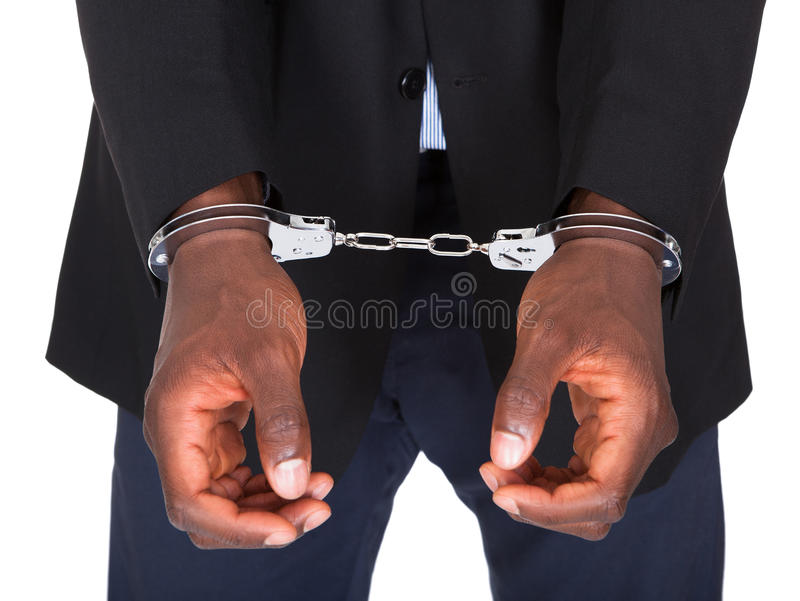 Uomo arrestato con le mani ammanettate fotografia stock