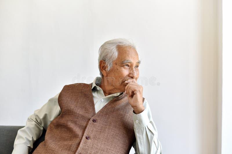 Uomo asiatico anziano infelice con attento il gesto di considerazione, uomo anziano solo che guarda fuori la preoccupazione della immagini stock