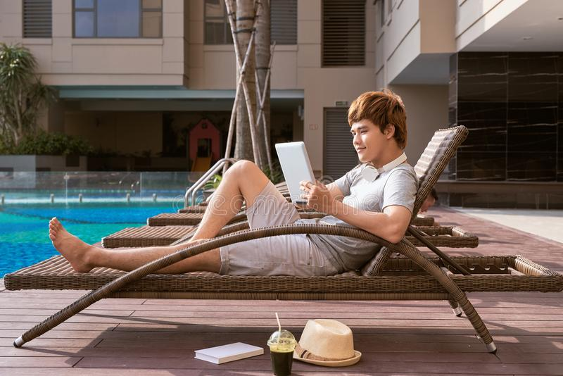Uomo asiatico bello che si rilassa dallo stagno e che legge libro elettronico fotografia stock libera da diritti