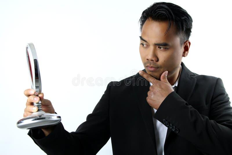 Uomo asiatico che ammira nello specchio immagini stock