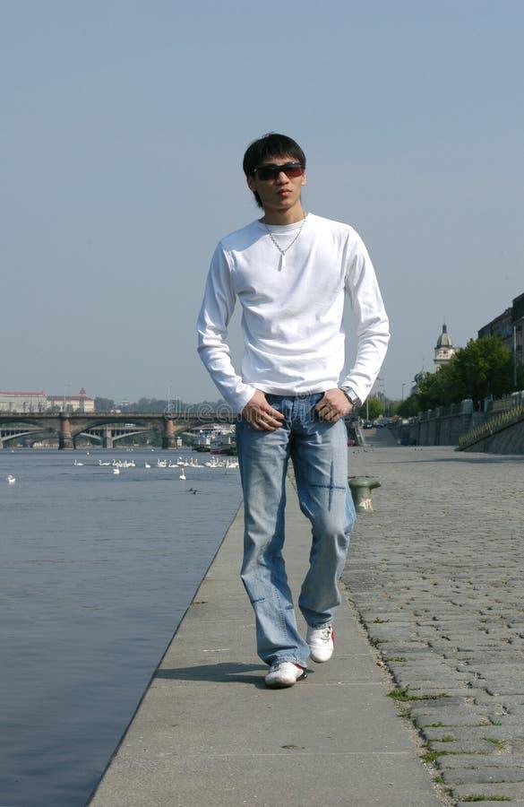Uomo asiatico che cammina lungo l'argine immagine stock libera da diritti