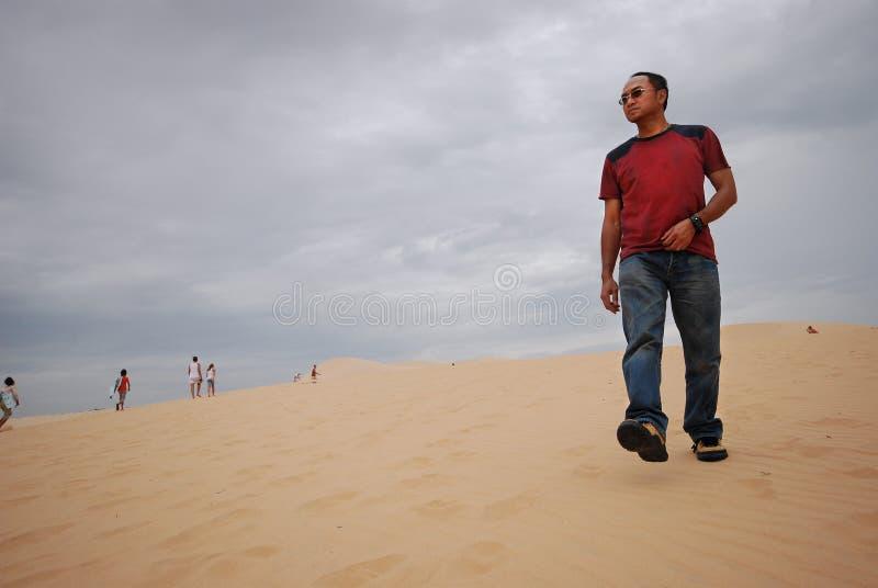 Uomo asiatico che cammina su una duna di sabbia del deserto nel Vietnam, Muine fotografia stock libera da diritti