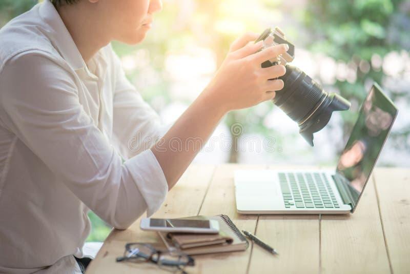 Uomo asiatico che controlla foto sulla macchina fotografica digitale fotografia stock