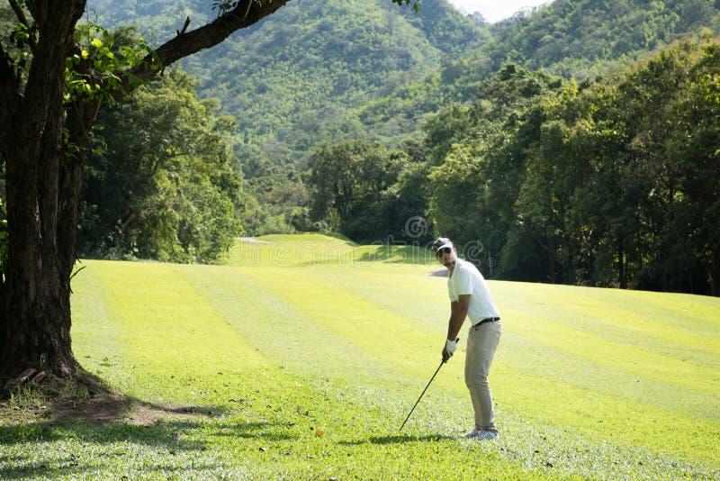Uomo asiatico che gioca golf su un bello campo da golf naturale fotografia stock libera da diritti