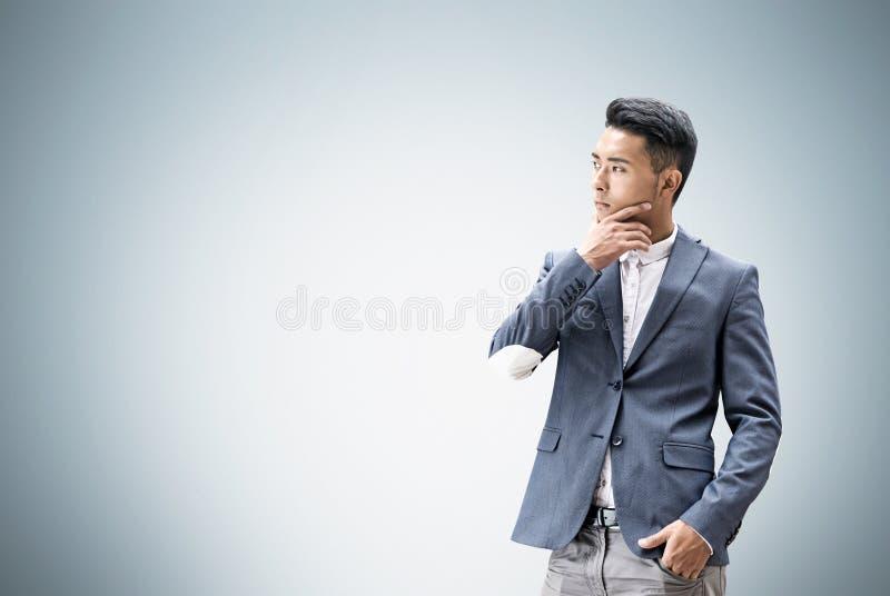 Uomo asiatico che pensa vicino alla parete grigia fotografia stock libera da diritti