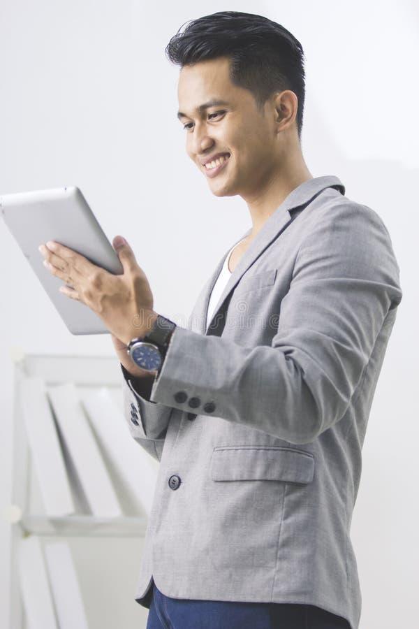 Uomo asiatico che per mezzo del pc della compressa fotografia stock