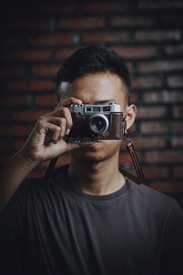 Uomo asiatico che prende immagine con la macchina fotografica d'annata sul muro di mattoni immagini stock