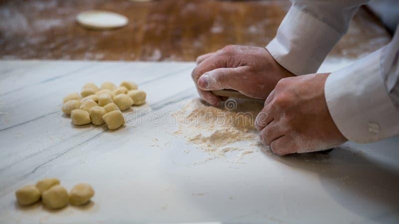 Uomo asiatico che produce gli gnocchi freschi in un ristorante della cucina di Taiwan fotografia stock libera da diritti