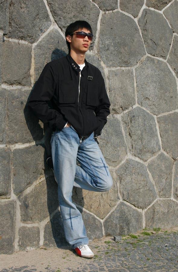 Uomo asiatico che si appoggia contro una parete fotografia stock libera da diritti