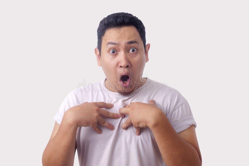 Uomo asiatico che si indica con l'espressione infelice come se confonda per essere accusato fotografia stock