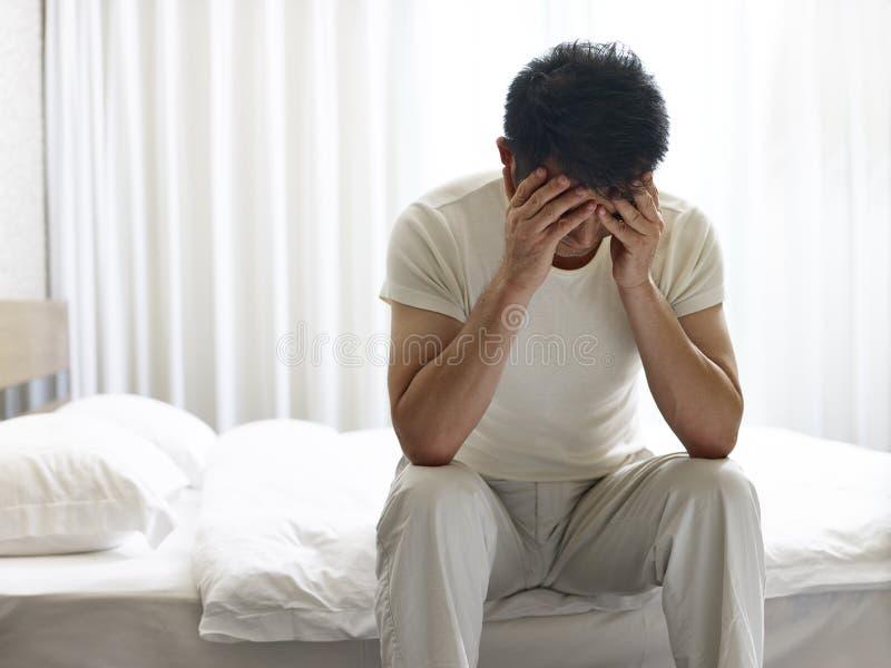Uomo asiatico che si siede sulla testata del letto giù che copre fronte di mani fotografia stock libera da diritti