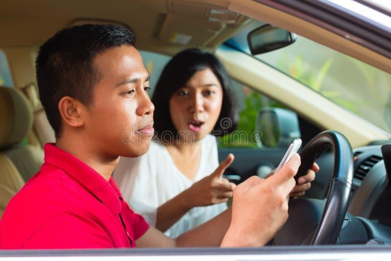 Uomo asiatico che texting mentre guidando immagine stock