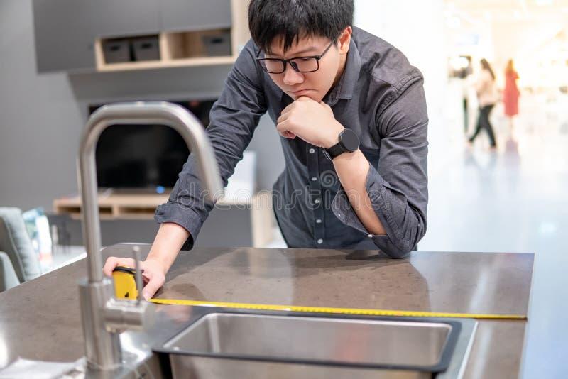 Uomo asiatico che usando misura di nastro sul contatore di cucina fotografia stock libera da diritti