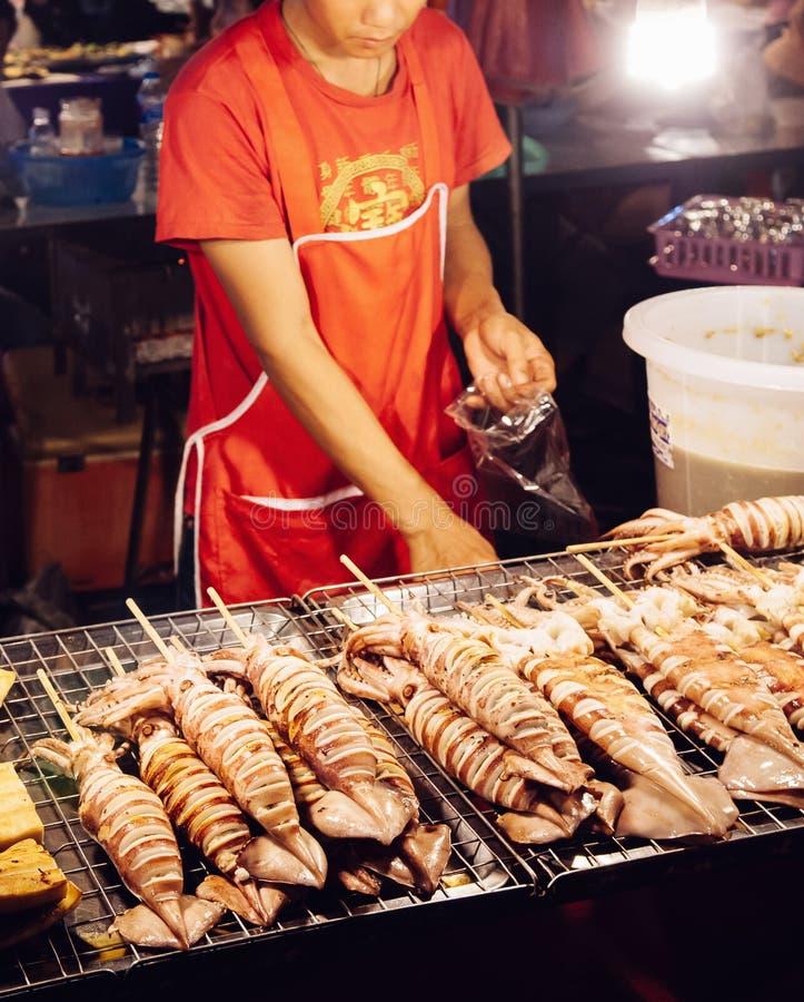 Uomo asiatico che vende lo spiedo dei calamari della griglia al colpo del mercato dell'alimento della via fotografie stock libere da diritti