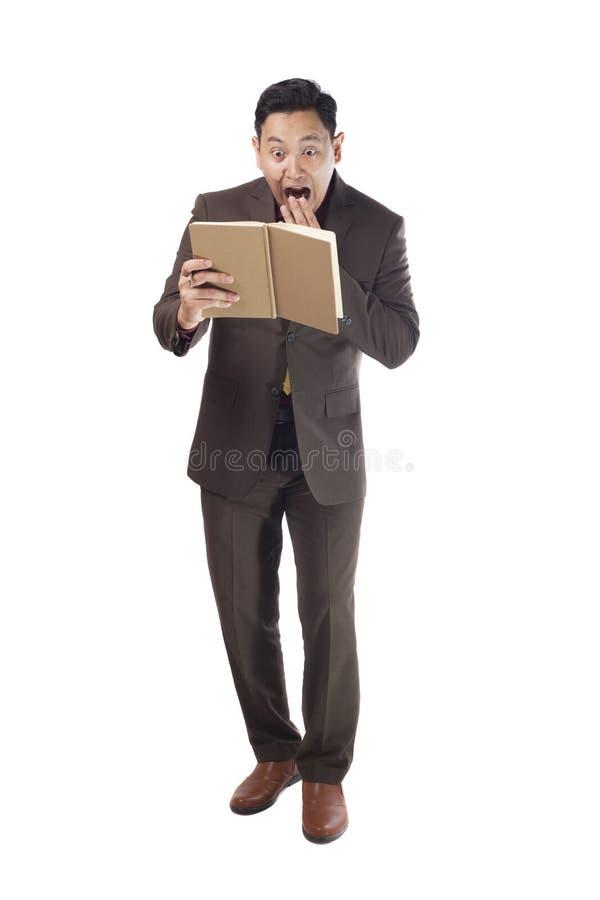 Uomo asiatico colpito sorpreso quando leggono un libro immagini stock