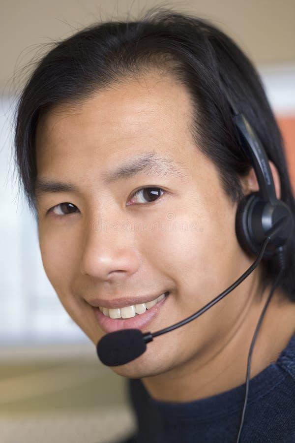 Uomo asiatico con la cuffia avricolare fotografia stock