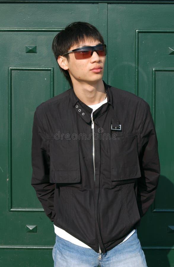 Uomo asiatico davanti ad un portello immagine stock