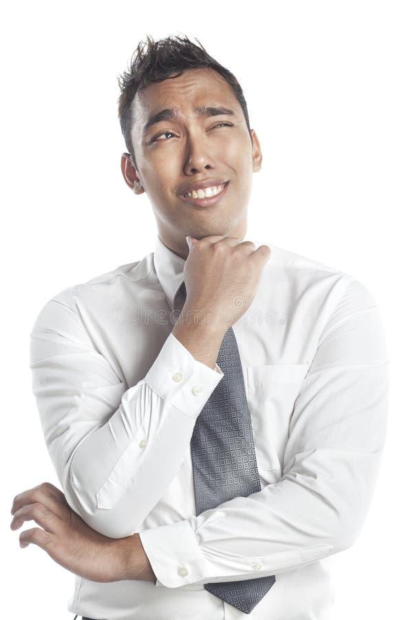 Uomo asiatico del Malay che sorride con un'espressione imbarazzata fotografie stock libere da diritti