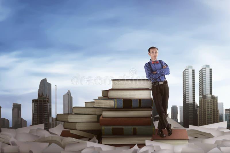 Uomo asiatico del nerd che si appoggia i grandi libri fotografia stock libera da diritti