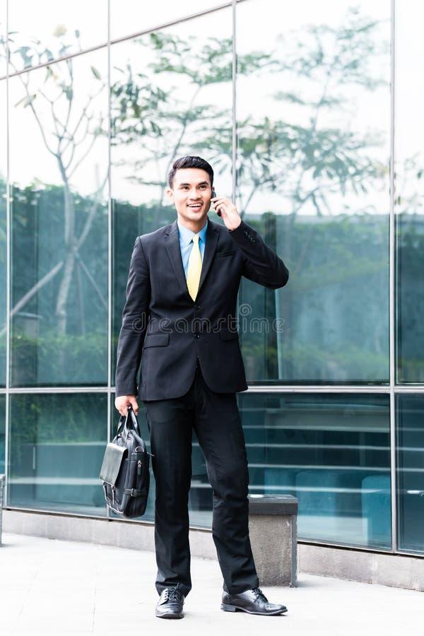 Uomo asiatico di affari che parla con telefono cellulare fuori immagine stock
