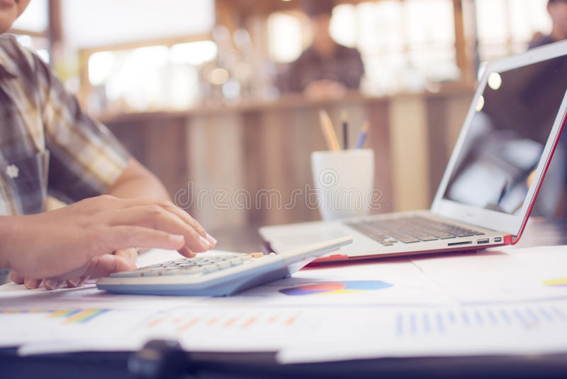 Uomo asiatico di affari che per mezzo di un calcolatore per calcolare i numeri w immagini stock libere da diritti