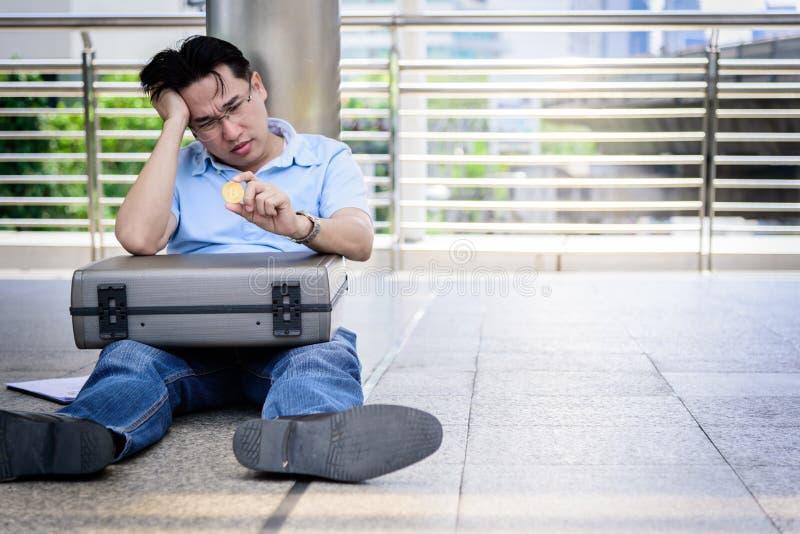 Uomo asiatico di affari che si siede nella depressione con i soldi della moneta del pezzo fotografia stock