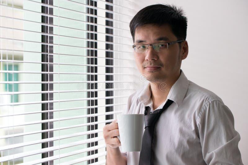Uomo asiatico di affari con una tazza di caffè immagine stock
