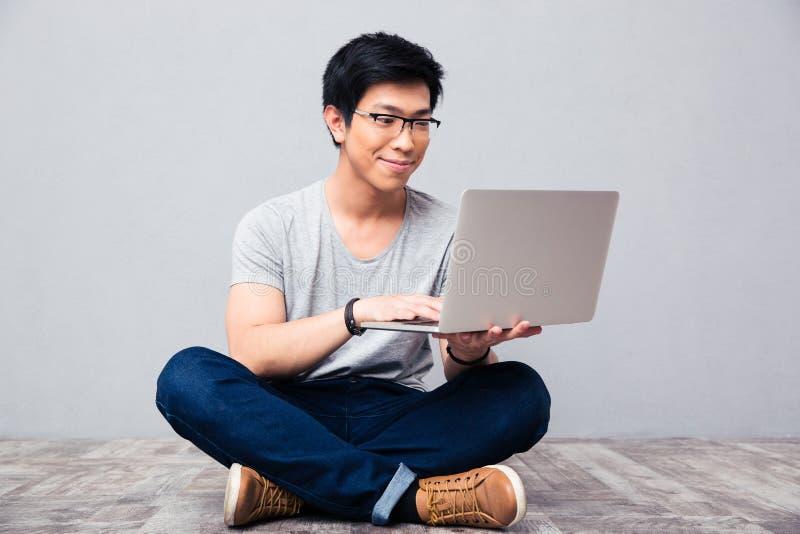 Uomo asiatico felice che per mezzo del computer portatile fotografie stock libere da diritti