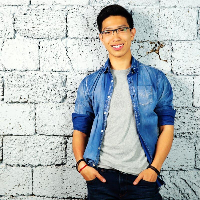 Uomo asiatico felice che si appoggia muro di mattoni immagini stock libere da diritti