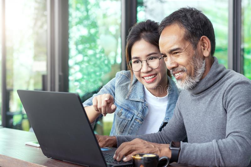 Uomo asiatico maturo attraente con la breve barba alla moda bianca che esamina computer portatile con la donna adolescente dei pa immagini stock libere da diritti