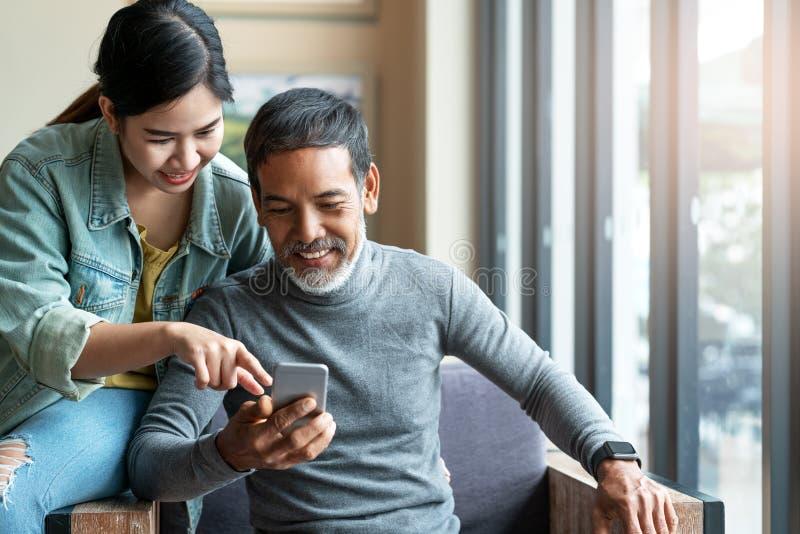 Uomo asiatico maturo attraente con la breve barba alla moda bianca che esamina il computer dello smartphone con la donna adolesce fotografia stock libera da diritti