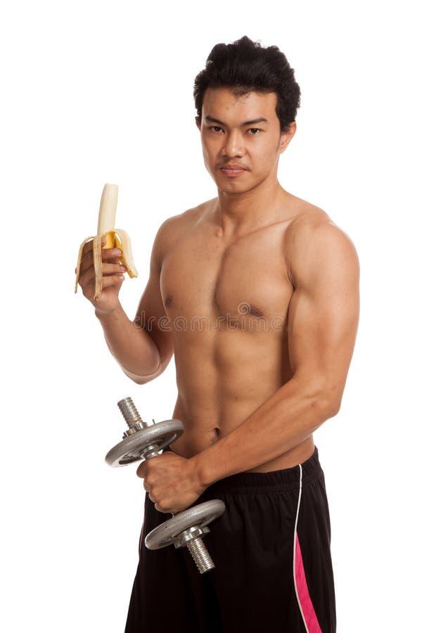 Uomo asiatico muscolare con la banana e la testa di legno fotografie stock libere da diritti