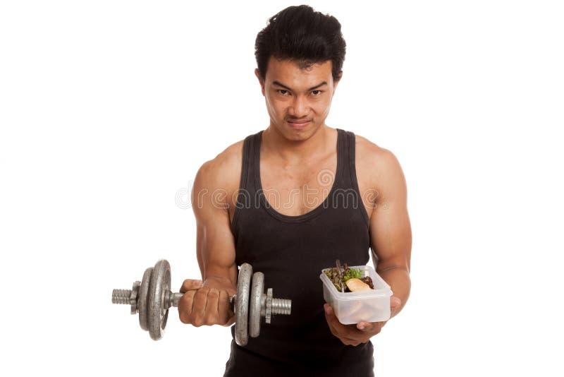 Uomo asiatico muscolare con la testa di legno ed alimento pulito in scatola immagine stock libera da diritti