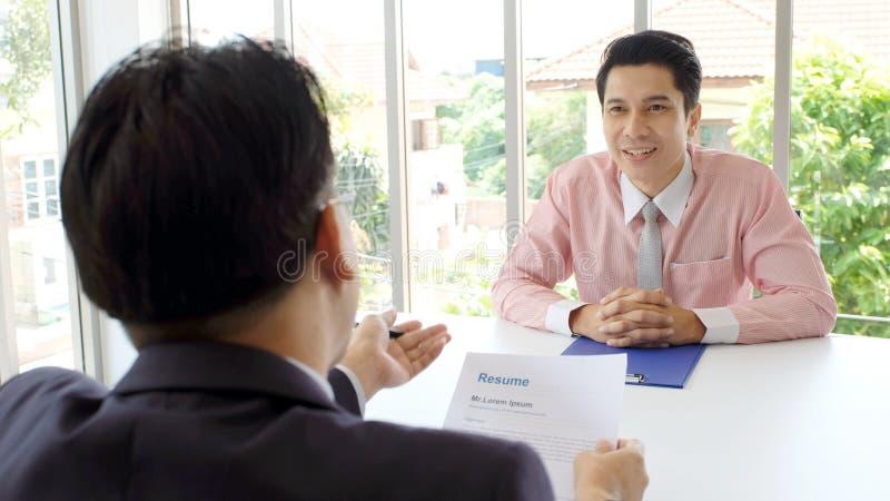 Uomo asiatico nell'intervista di lavoro al fondo dell'ufficio, ricerca di lavoro, concetto di affari fotografia stock