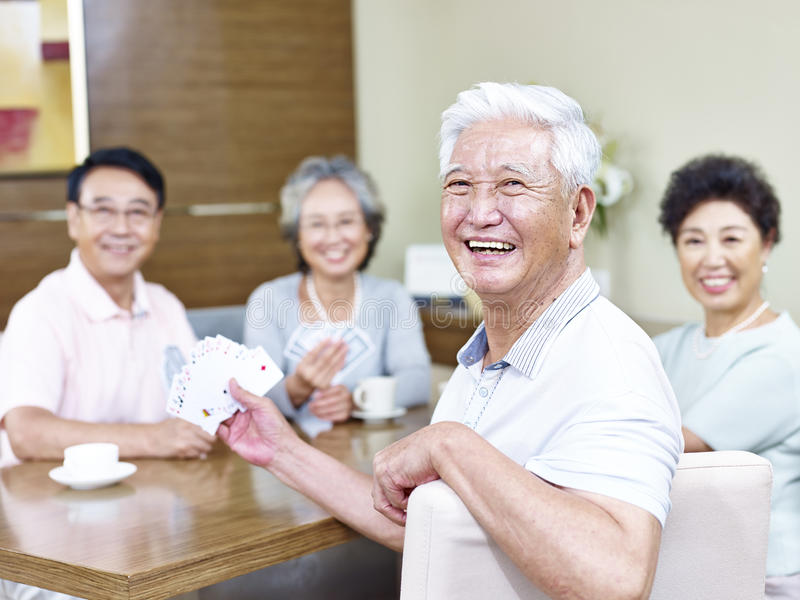 Uomo asiatico senior in carte da gioco con gli amici immagine stock