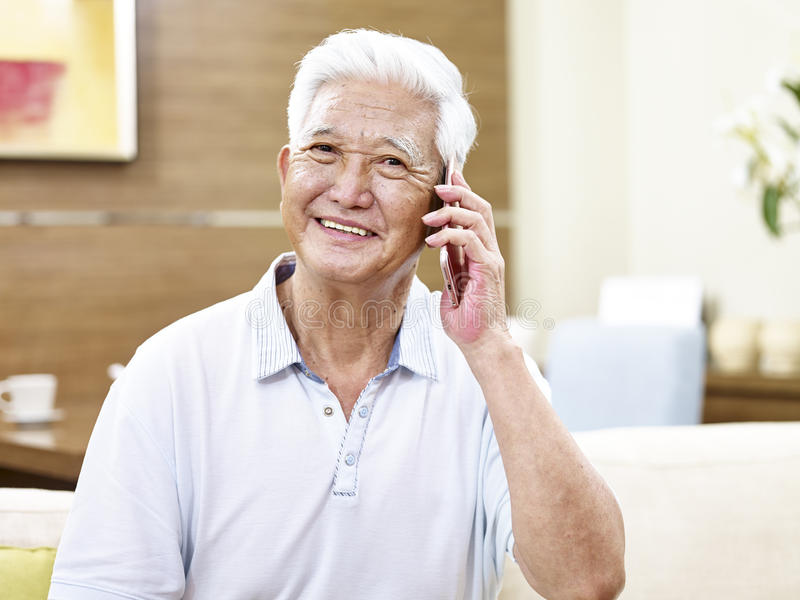 Uomo asiatico senior che fa una chiamata fotografia stock