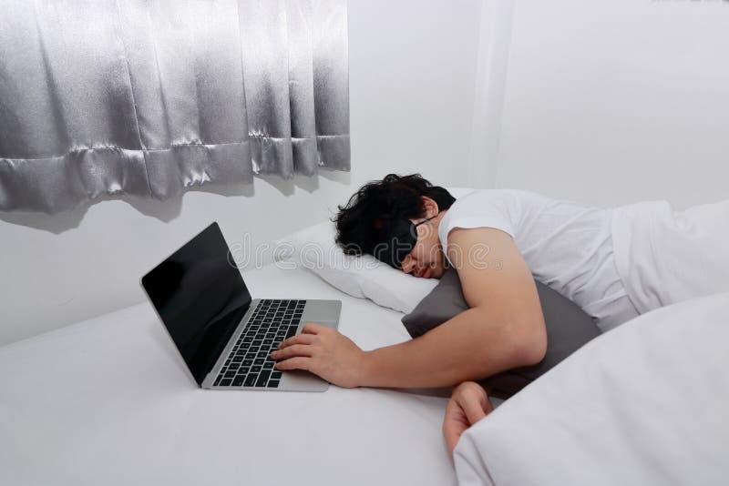 Uomo asiatico sovraccarico stanco con il computer portatile che dorme sul letto fotografia stock libera da diritti